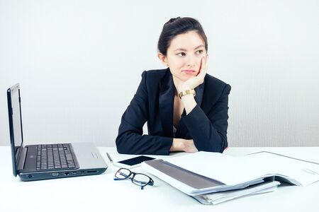 attractive displeased unhappy brunette businesswoman in a stylish business suit working in the office with a laptop and bored.