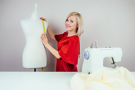Beautiful girl seamstress designer measures a mannequin. Sewing machine and white background