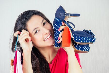 beautiful smiling brunette woman shopaholic holding a stylish shoes with a red label tag , tab , tally in her hand . concept of seasonal sales and shopping