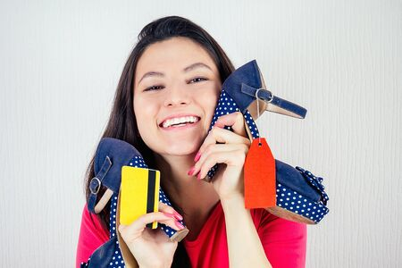 beautiful smiling brunette woman shopaholic holding a stylish shoes with a red label tag , tab , tally and a plastic credit card in her hand . concept of seasonal sales and shopping