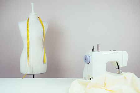 the workplace of a seamstress: the sewing machine, a mannequin with a yellow measuring tape and white background