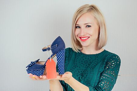 beautiful smiling blonde woman shopaholic holding a stylish shoes with a red label tag , tab , tally in her hand . concept of seasonal sales and shopping