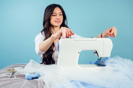 attractive brunette woman seamstress tailor dressmaker thread the needle on the sewing machine on a blue background in the studio. The concept of creating a new collection of clothes Stock Photo