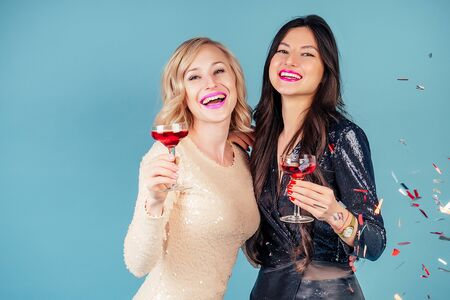 two happy and attractive girlfriends brunette and blonde womens in evening cocktail shiny sequins dress are holding a glass of wine at a party in the studio blue background