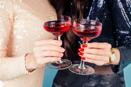 hands of two womens in evening cocktail shiny sequins dress are holding a glass of wine at a party in the studio blue background Stock Photo