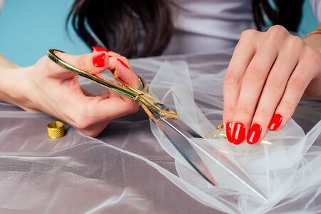 seamstress tailor dressmaker womans hands with red manicure holds scissors and cuts fabric on table in the studio.