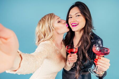 two happy and attractive girlfriends brunette and blonde womens in evening cocktail shiny sequins dress are holding a glass of wine and do selfie on the phone at a party in the studio blue background Stok Fotoğraf