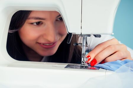 close-up portrait attractive woman seamstress tailor dressmaker thread the needle on the sewing machine on a blue background in the studio. The concept of creating a new collection of clothes Stock Photo