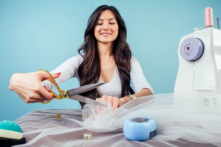 attractive brunette woman seamstress tailor dressmaker holds scissors and cuts fabric on table with sewing machine on a blue background in the studio.