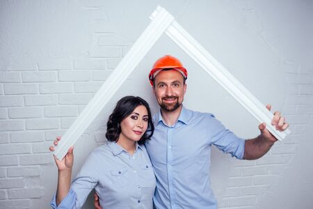 happy family handsome man in the construction helmet hardhat and charming woman together are building the roof house . concept of buying a cozy and warm apartment by young newlyweds