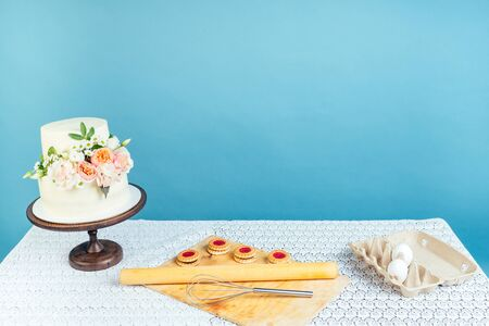 copyspace mockup working space baker confectioner pastry chef creamy white two-tiered wedding birthday cake with fresh flowers on table and cookies in studio on blue background