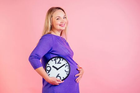 beautiful and smiley blonde pregnant woman holding a clock in hands in studio on a pink background . time for birth concept Stok Fotoğraf
