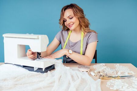attractive blonde woman seamstress tailor dressmaker sews a wedding dress for the client prom sewing machine on a blue background in the studio.