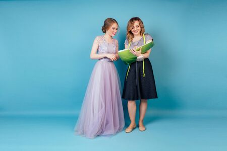 beautiful coordinator seamstress woman and bride discuss the details of wedding dress in the studio on a blue background . tailor dressmaker and customer prom