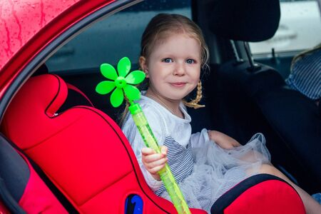 little and sweet blonde girl in a cute gray dress beautiful sitting in the red car child seat seat for childrenin