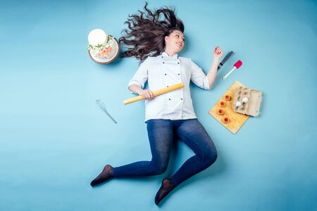 top view from above of confectioner pastry chef baker woman around wedding birthday cake , cookies ,eggs, whisk and rolling pin lying run on the floor in studio on blue background. 写真素材