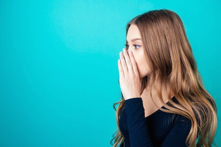portrait of a young attractive happy woman with blonde hair and makeup whispers a secret mystery in the studio on a blue background. the concept of gossip and confidentiality
