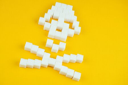 The bones skull made of sugar cubes on a yellow background. Sugar kills and diabetes concept