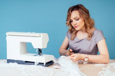 attractive woman seamstress tailor dressmaker holds scissors and cuts fabric on table with sewing machine on a blue background in the studio.