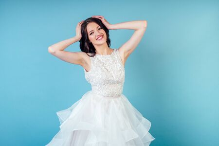 młoda i piękna kobieta panna młoda z makijażem w długiej eleganckiej białej sukni ślubnej w studio na niebieskim tle