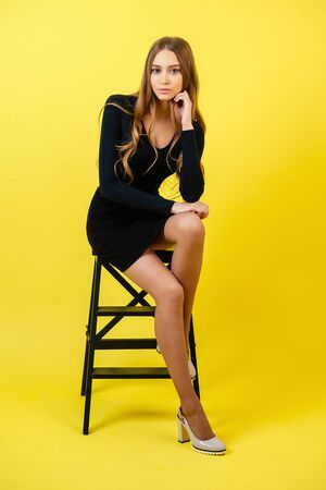 attractive woman model with long hair in black tight sexy dress and high-heeled shoes sits on chair and posing on yellow background in studio