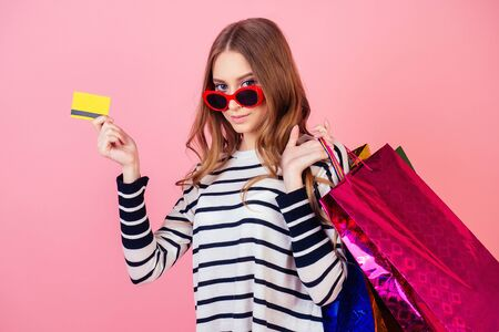 stylish and young attractive woman in a striped sweater and red sunglasses holds many shopping bags and credit card on a pink background in the studio. concept of shopaholism and sale 版權商用圖片