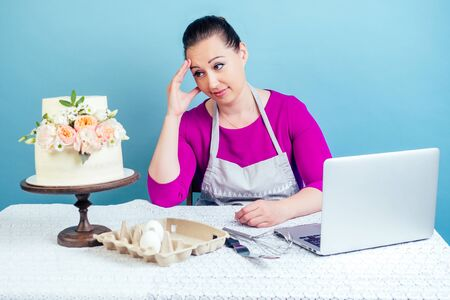 confectioner housewife pastry-cook businesswoman looks disappointed at the white two-tiered wedding cake with fresh flowers on a table in studio on a blue background