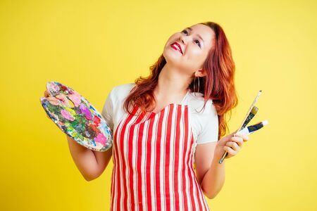 portrait of a beautiful artist in an apron holding a palette and brush on a yellow background in the studio Фото со стока