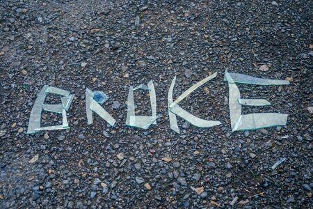 inscription with broken glass lying on the asphalt