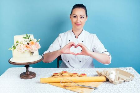 confectioner pastry chef woman shows fingers heart symbol next to creamy white two-tiered wedding birthday cake with fresh flowers on table in studio on blue background. the concept of love of work