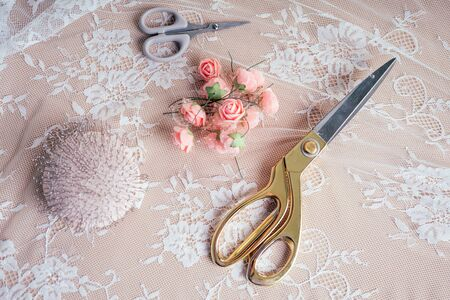 close-up handen van vrouw naaister kleermaker kleermaker ontwerper trouwjurk naait kralen aan kant op een blauwe achtergrond in de studio Stockfoto