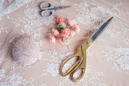 gros plan mains de femme couturière tailleur couturière designer robe de mariée coud des perles à la dentelle sur un fond bleu dans le studio Banque d'images
