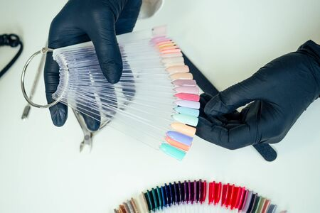 close-up hands of manicurist professional master of manicure woman in a white jacket and black rubber gloves is choose a palette of colors nail polish in a beauty spa salon.