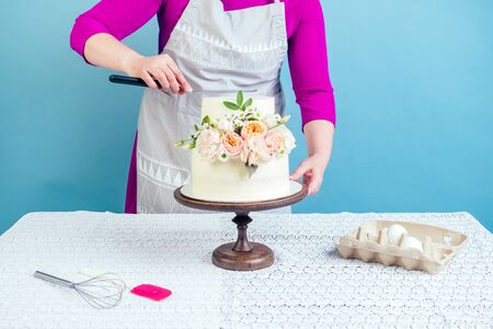 woman confectioner pastry-cook decorate appetizing creamy white two-tiered wedding cake decorated with fresh flowers on a table with a lace tablecloth in studio on a blue background Stockfoto