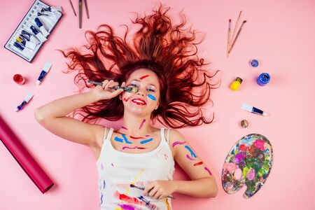 beautiful fun dirty artist painter red-haired stains blot from paint on the face lying on the floor next to palette, tube of paint , brushes on a pink background in studio Фото со стока