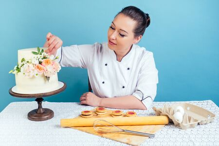 confectioner pastry chef baker woman decorates creamy white two-tiered wedding birthday cake with fresh flowers on table in studio on blue background. concept of a holiday and preparation event