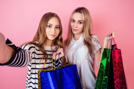 Two beautiful and smiling female person mother and daughter holding a lot of shopping bags and do selfie on the phone on a pink background in the studio. concept of sale and shopping