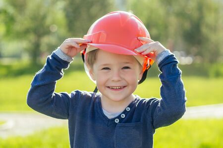 portrait of cute european little boy in a construction helmet in the park on a background of green grass and trees . career guidance builder concept Фото со стока