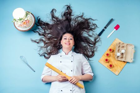 top view from above of confectioner pastry chef baker woman with long dark hair around wedding birthday cake , cookies eggs, whisk and rolling pin lying on the floor in studio on blue background.