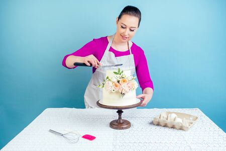 confectioner female person pastry-cook decorate appetizing creamy white two-tiered wedding cake decorated with fresh flowers on a table with a lace tablecloth in studio on a blue background Standard-Bild