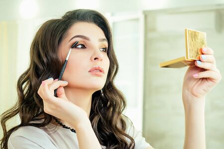 portrait of attractive and beautiful woman make-up artist visagiste sitting in front of a mirror and applies eyeshadow cosmetics make-up on face in salon studio. concept of self-care and self-love