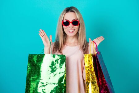 portrait of a stylish and attractive crazy shopaholic woman in red sunglasses holding a lot of shopping bags surprised and shocked on a blue background in the studio. concept of shopaholism and sale 版權商用圖片