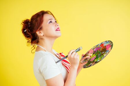 portrait of a beautiful artist in an apron holding a palette and brush on a yellow background in the studio . inspiration and muse idea Фото со стока