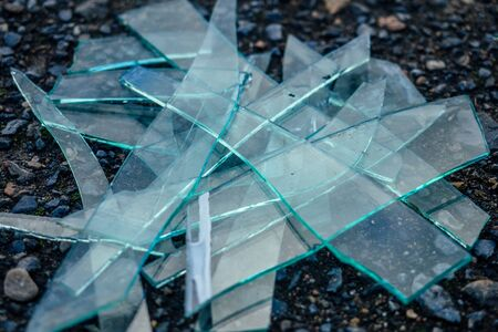 a small pile of broken glass lying on the asphalt Stok Fotoğraf