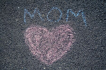 painted colored chalk crayons heart word mom on the asphalt . concept of love and mothers day