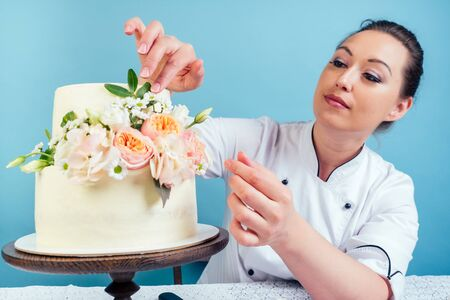 confectioner woman pastry-cook in confectioners jacket decorate appetizing creamy white two-tiered wedding cake with fresh flowers on a table with a lace tablecloth in studio on a blue background
