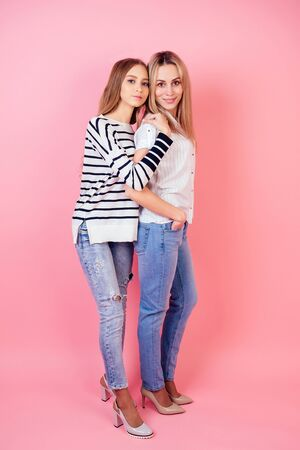 beautiful and smiling mother and daughter in jeans and stylish high-heeled shoes posing on a pink background in the studio. concept family well-being and love