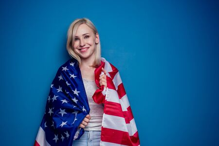 blonde woman in jeans holding American flag with paper crown and torch Statue of liberty on a blue background in the studio .4th july independence day celebration concept
