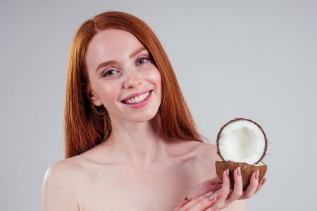 young ginger redhead woman with ideal skin and perfect redhaired hear holding coco nut in hands in white studio backgroung. Stok Fotoğraf