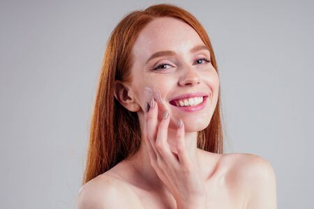 fashion portrait of redhead model nude with perfect skin studio on white background.